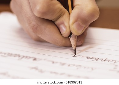 School Boy Writing Close Up. Pencil in Children Hand.