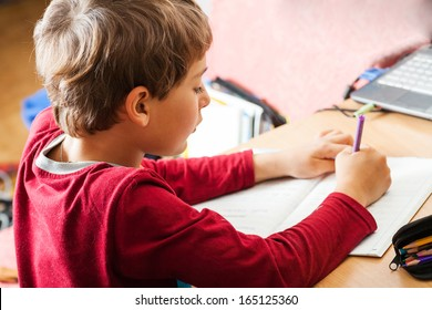 School boy writing indoors. Child studing with notebook. Education, elementary school, learning people concept - school kid writing test in classroom