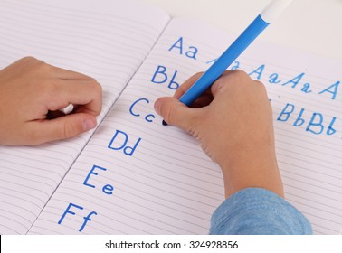 School Boy Writing on Paper writing the alphabet with Pencil . Kid, homework, education concept. Selective focus image