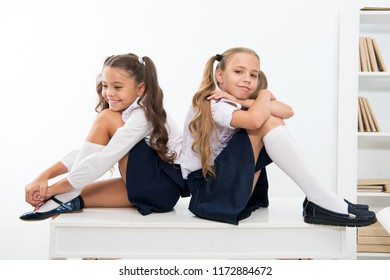 School break concept. Schoolgirls cute pony tails hairstyle sit on desk. Best friends free relaxing after classes. Perfect schoolgirls with tidy fancy hair relaxing or having rest after lessons.