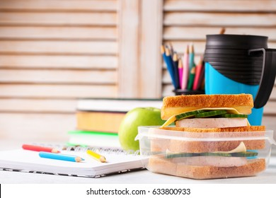 School break. Sandwich with ham, cheese and a cucumber in a lunchbox. Food and stationery. Selective focus.