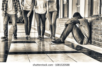 School bullying. Afro american male teenager upset seated in school hallway while group of teenagers walk towards him.