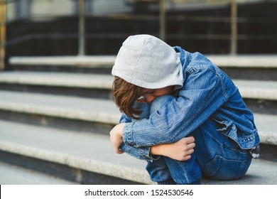 School bullying concept. Kid boy sitting at stair, covering his face. Sad young schoolboy outside school. Negative emotion, depression, stress.