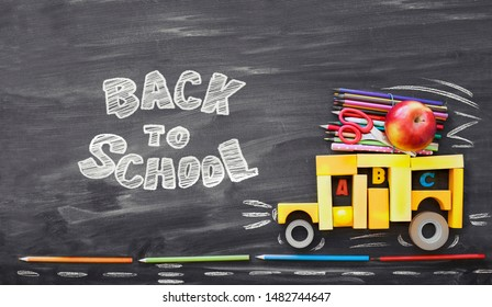 School bus with apple and pencils  over classroom blackboard background/ top view/Back to school concept.