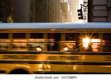 School bus in motion streaking down Fifth avenue Manhattan New York at Sunrise with the sun flaring through the windows.