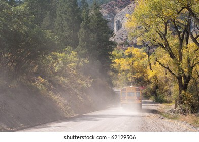 School bus on a rural dirt road in autumn