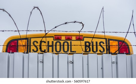 School bus parked behind barbed wire fence
