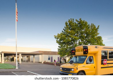 A school bus waits outside of a small high school.