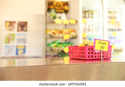 school canteen tuck shop cafeteria selling healthy fruit food options for students. bananas in a red tray on stainless steel bench with stands of blurred chip packets and fridge with drinks behind.