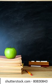 A school chalkboard and teacher's desk with stack of exercise books and an apple. Copy space on blackboard.  Portrait (vertical) orientation.