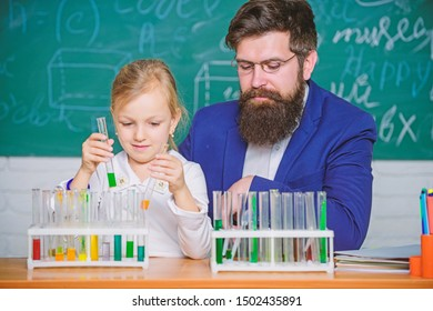 School chemistry experiment. Explaining chemistry to kid. How to interest children study. Fascinating chemistry lesson. Man bearded teacher and pupil with test tubes in classroom. Private lesson.