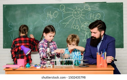 School chemistry experiment. Explaining chemistry to kids. Fascinating chemistry lesson. Man bearded teacher and pupils with test tubes in classroom. Observe reaction. Science is always the solution.