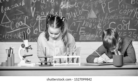 School chemistry lesson. School laboratory. Girl and boy smart students conduct school experiment. Describe chemical reaction notepad. School education. Chemical analysis. Kids busy study chemistry.