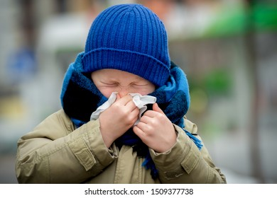 School child boy blow his nose. Sick child with napkin in autumn park. Allergic kid, flu season. Kid with cold rhinitis, get cold. Back to school