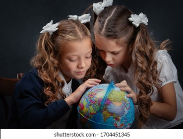 School child girls with a globe at dark background.