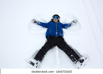 School child, making snow angels in the snow, while skiing in ski resort in Austria