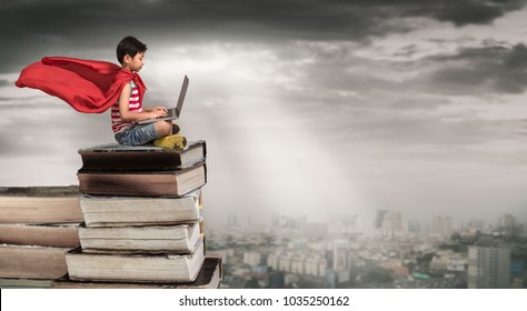 School child using laptop on the books.Study and education concept.Super hero boy sitting on a pile of books.