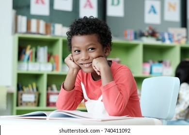 School children, African boy, Black kid, American child student read, sit and smile with happiness at classroom, kindergarten, pre school education concept