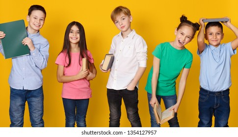 School children with books having fun on yellow studio background