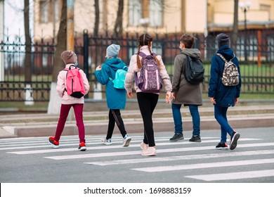医療用マスクを着て学校の子どもが道を渡る。子どもは学校へ行く