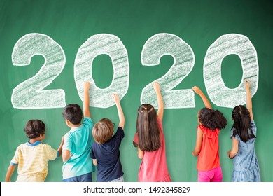 school children drawing 2020 new year on the chalkboard