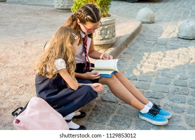 School children, girls of high and primary school together read textbook. Time after school at the street sidewalk