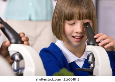 School children looking into microscopes in classroom laboratory