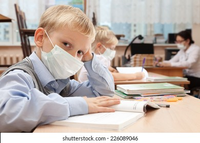 School children in medical face mask are learning in the half empty classroom during epidemic of flu.