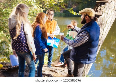 School children. Nice red haired girl looking at her teacher while holding a picture with a polar bear