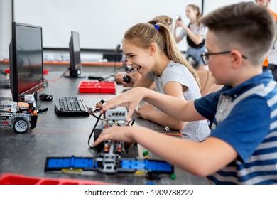 Schulkinder programmieren einen Roboter im Klassenzimmer