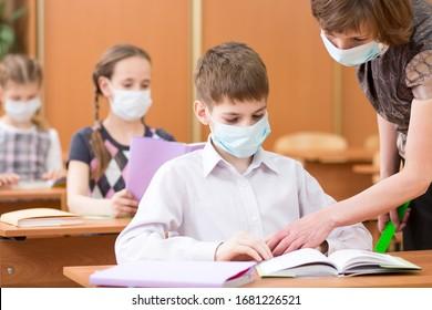 Schulkinder mit Schutzmasken gegen Coronavirus im Unterricht im Klassenzimmer