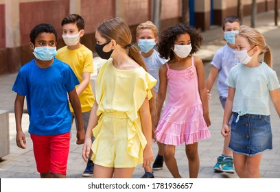 School children in protective medical masks walk along the street of a summer city