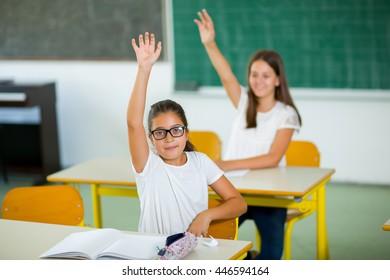 School children raised hands in class