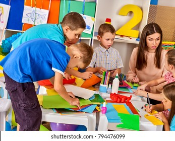 School children with scissors and cutting color paper . Kids and teacher in class room. Development and social lerning. Children's project in kindergarten. Preparation for origami exhibition.