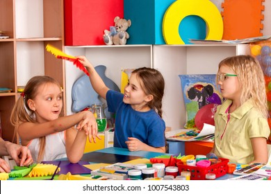 School children with scissors in kids hands cutting paper with teacher in class room. Children's project in kindergarten zone. Large group girls and boys together. Team of students makes paper fans.