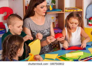 School children with scissors in kids hands cutting paper with teacher in class room. Children's project in kindergarten. Social Development of large group girls and boys together.