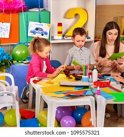 School children with scissors in kids hands cutting paper with teacher in class room. Development and social lerning. Children's project in kindergarten. Hobby for teenagers.