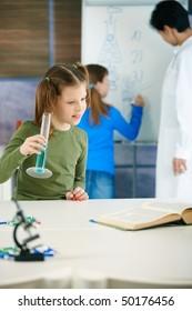 School children and teacher in classroom at elementary school in science class.
