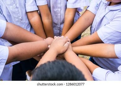 School children use hand-to-hand coordination to combine power in activities.