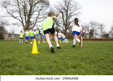 School children wearing sports uniform running around cones during a physical education session.