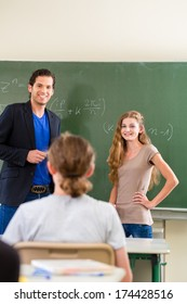 School class Teacher or educator testing in a lessons students in front of the class at the blackboard or board or chalkboard in math
