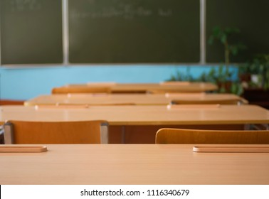 School classroom with school desks and blackboard in high school. Empty classroom background.