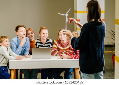 School Classroom: enthusiastic female teacher showing wind turbine explained to a brilliant different age children how wind turbines work. Kids learning about eco-friendly forms of renewable energy.
