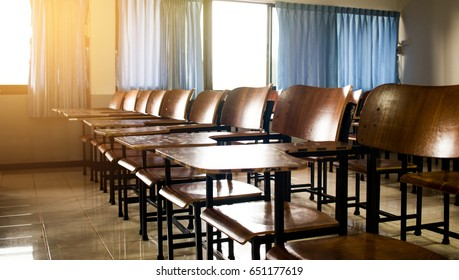 School classroom with old, dirty lecture wooden desk and chair in high school thailand, vintage tone education concept