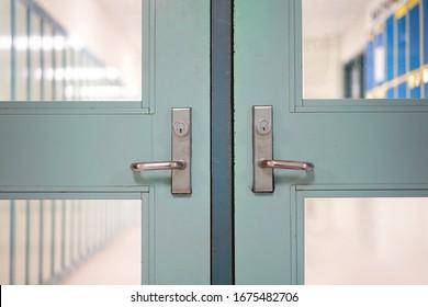 School closed due to Coronavirus variant spread.  School closure under surge COVID-19 global pandemic. Double door handles,  blurred hallway locker background. Fight against public health risk disease