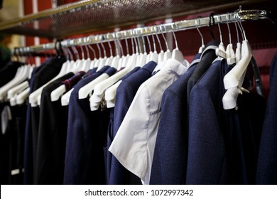 School clothes for boy and girl on hanger