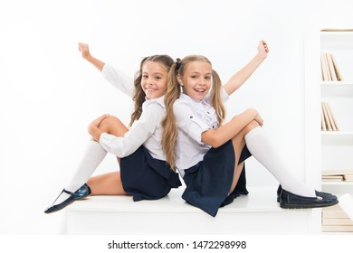 School club. Little schoolgirls classmates friendly kids. Schoolgirls friends sit on desk. Best friends relaxing. Schoolgirls tidy hairstyle relaxing having rest. School uniform. Rebellious spirit.