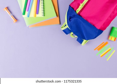 School concept flat lay. Kid backpack, lunchbox, water bottle, notebook, markers on wooden desktop