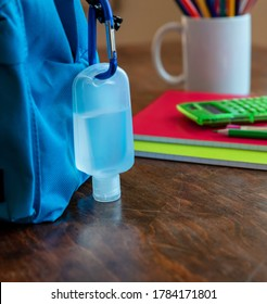 School, coronavirus days. Hand sanitizer gel and school bag backpack on wooden desk background, close up view, copy space