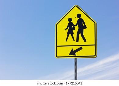 School crosswalk and arrow sign.